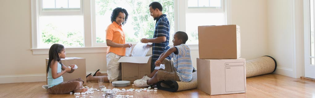 Family packing boxes to represent moving